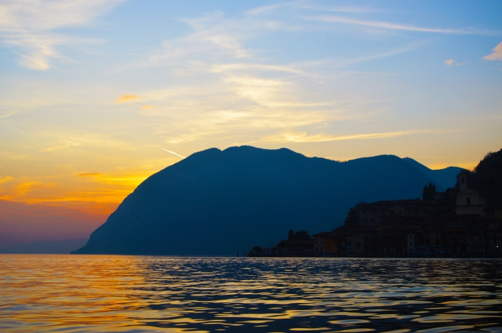 lake iseo, island monte isola. italy photography, travel blog, sunrise over mountains and little town on the lake