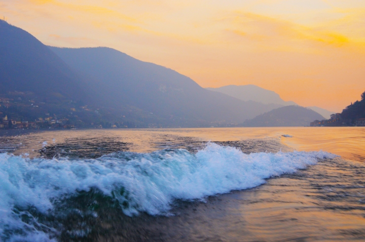 lake d'iseo in italy, boat trip, photography of lake and waves, sunrise over mountains and little town on the lake